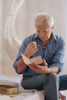 Unhappy gloomy senior man holding an old postcard and reading it while sitting on the bed