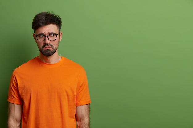 Unhappy gloomy young european man looks upset and disappointed, wears casual orange t shirt and spectacles, feels uneasy and moody, stands against green wall, copy space for your promotion.