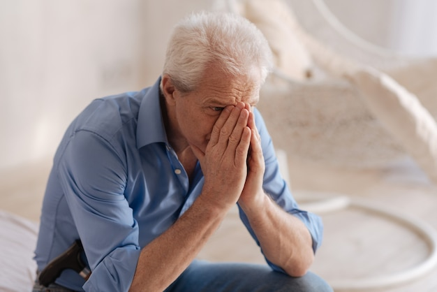 Unhappy grey haired senior man covering his face and crying while not being able to hold his feelings