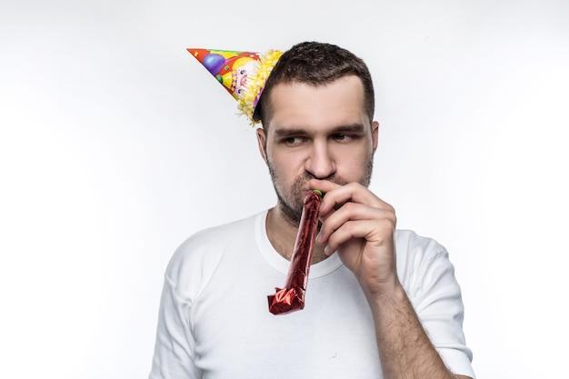 Несчастный парень на вечеринке. он не знает, как оставаться счастливым и блистательным во время праздника. изолированные на белом фоне