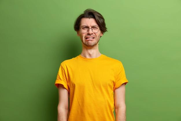 不幸なハンサムな白人男性は絶望の中で叫び、絶望的な笑い顔を感じます