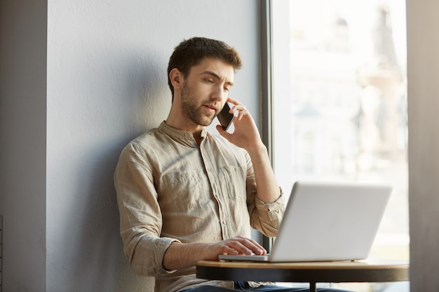 Несчастный красивый парень с темными волосами, сидя в кафе, работает на ноутбуке и разговаривает с недовольным клиентом по телефону.