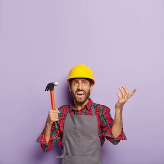 Unhappy handyman holds hammer, focused above with annoyance, repairs something with building tool in workshop, wears hardhat, shirt and apron. foreman inspector at work, does repairing alone