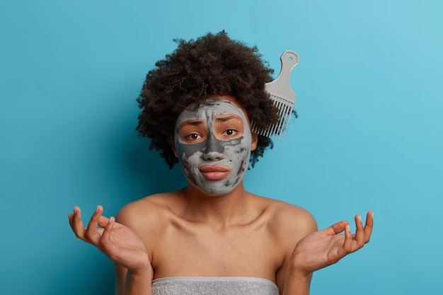 Unhappy hesitant afro american woman with comb stuck in frizzy natural hair, spreads hands sideways with puzzlement, doesnt know how to comb, wears cosmetic face mask, bath towel around body