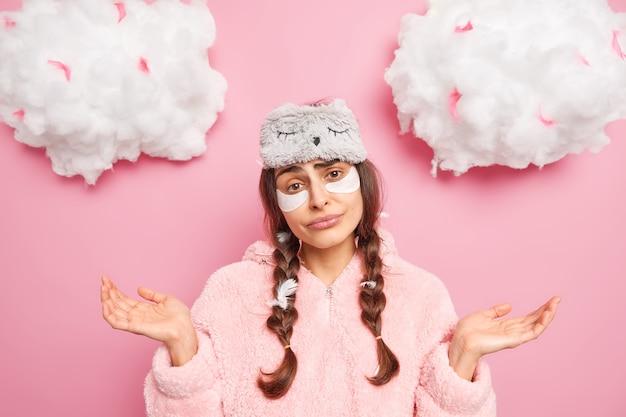 不幸な躊躇している女性が手のひらを広げ、正面が疑わしいように見える寝間着を着たこの日は何をすべきかわからないバラ色の壁に隔離されたスキンケア手順を受けます