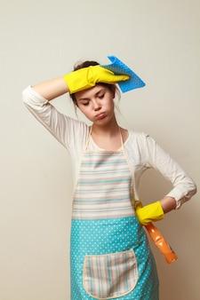 不幸な主婦。真面目な掃除をした後、若い女性がぼろきれを手に立っている。家事の概念は負担