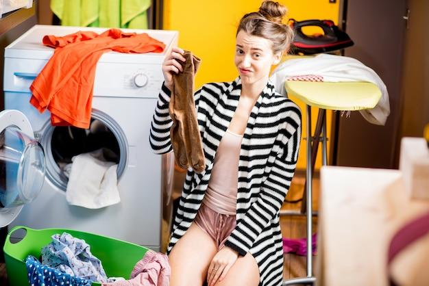 Несчастная домохозяйка держит носки возле стиральной машины с яркой одеждой дома