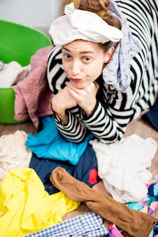 Несчастная домохозяйка сидит в носках возле стиральной машины с яркой одеждой на полу дома