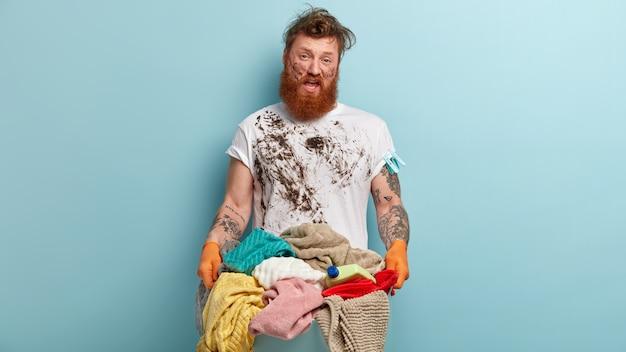 Uomo rosso infelice indignato con setole spesse, indossa una maglietta disordinata, guanti di gomma, porta un mucchio di biancheria, ha la faccia sporca, sta contro il muro blu, non è desideroso di fare il bucato a casa