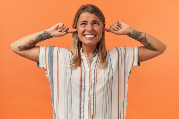 Unhappy irritated young woman in casual clothes closed ears by hands and do not want to listen noise isolated over orange wall