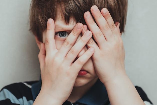Руки несчастного мальчика скрывают его лицо, концепция психического здоровья ребенка, всемирный день осведомленности об аутизме, концепция осведомленности о расстройствах аутистического спектра среди подростков