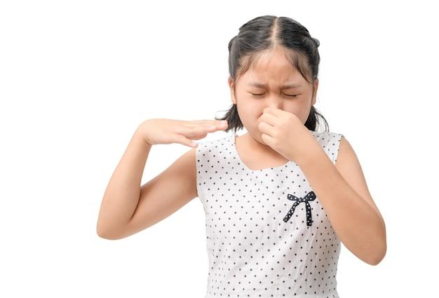 不幸な子供は気分が悪く、臭いが嫌いで、白い背景で隔離された臭い、変な臭いから鼻を保持します