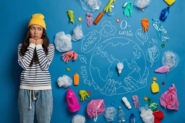불행한 한국 여성이 생태 프로젝트에 참여하고 심각한 환경 문제를 걱정하는 모든 플라스틱 쓰레기를 슬프게 바라보고 있습니다.