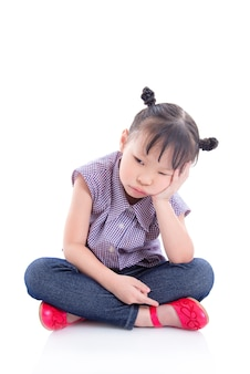 Unhappy little asian girl sitting on the floor isolated over white background