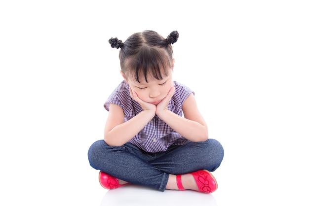 Unhappy little asian girl sitting on the floor