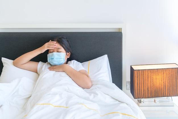 不幸な少年は、ウイルスや風邪の病気で気分が悪くなり、頭痛がして、自宅のベッドに横たわっている体温を測定します。