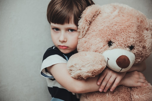 Unhappy little boy stand hugging stuffed teddy bear feel lonely lacking attention or communication, hurt small kid hold plush toy suffer from loneliness, need parents