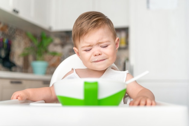 Unhappy little child with dirty messy face sitting in high chair baby cry refuse to eat