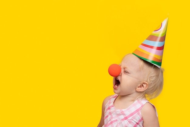 Unhappy little girl in festive hat and clown nose on yellow