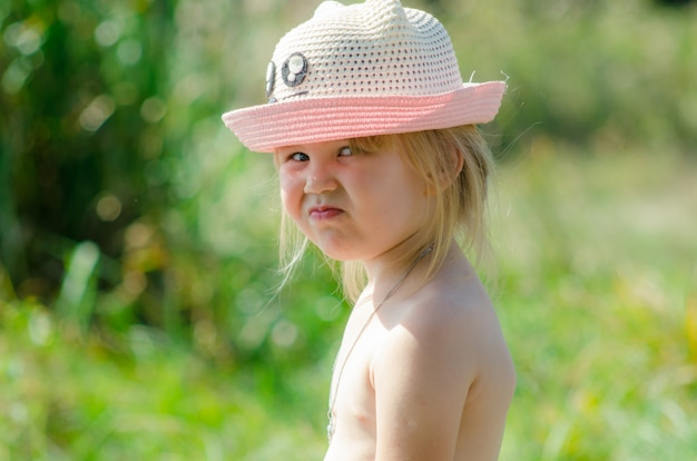 Unhappy little girl on summer vacation on nature