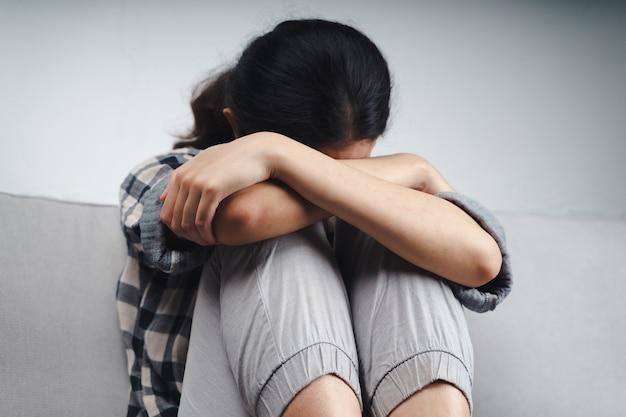 불행한 외로운 우울한 여성이 소파에 앉아 손으로 얼굴을 가리고 우울증 개념