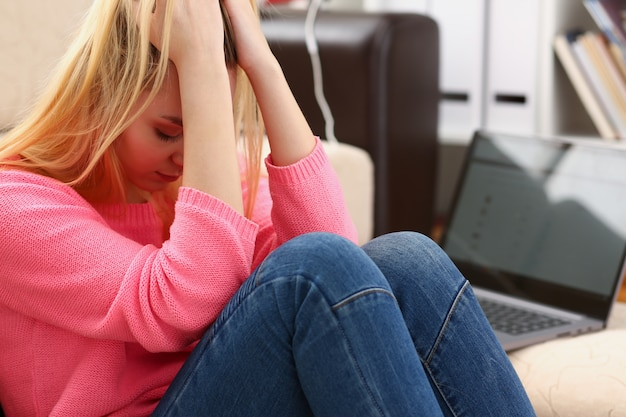 Unhappy lonely depressed woman sitting on the couch