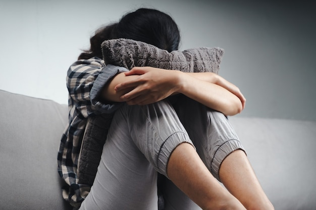 불행하고 외로운 슬픈 여성이 소파에 앉아 베개, 우울증 개념에 얼굴을 숨기고 있습니다