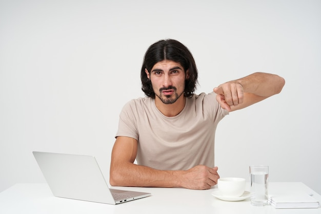Uomo d'affari dall'aspetto infelice e irritato con barba e capelli neri. concetto di ufficio. seduto sul posto di lavoro e puntare il dito su di te, isolato su un muro bianco