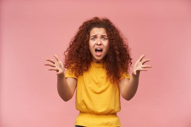 Donna dall'aspetto infelice, ragazza indignata con i capelli ricci di zenzero che indossa la maglietta gialla