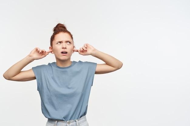 생강 머리를 가진 불행한 찾고 여자는 롤빵에 모였다. 파란색 티셔츠와 청바지를 입고. 손가락으로 귀를 닫으십시오. 복사 공간에서 오른쪽 상단 모서리를보고, 흰 벽 위에 절연