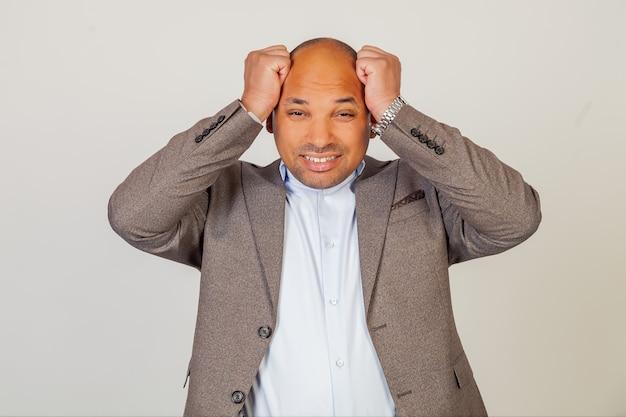 그의 머리에 그의 손을 잡고 재킷에 불행 한 남성 아프리카 계 미국인 사업가 매우 실망 하 고 회색 배경에 나쁜 소식 때문에 화가 카메라를보고.