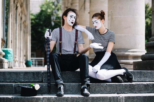 Unhappy male and female mime artist sitting on stairway