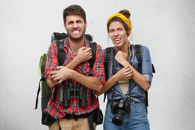 Unhappy male and female tourists with backpack, camera and binoculars, scratching their hands with unhappy look after walk in deep forest. people, adventure, travelling concept