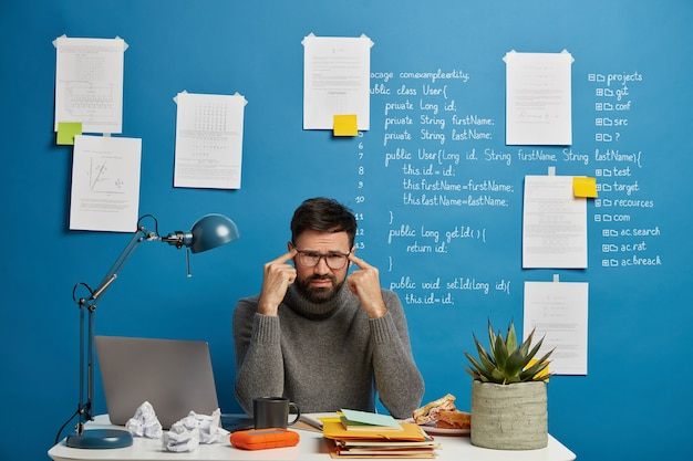 Unhappy male worker in spectacles sits at desktop during hard workday, keeps fingers on temples, suffers from headache, tries to concentrate on object, tired of overworking time at laptop computer
