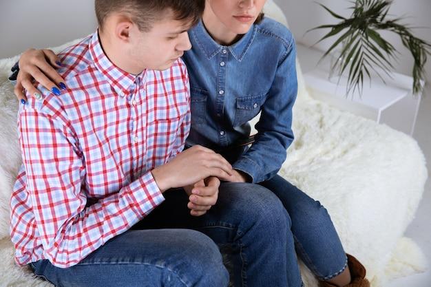 彼のソファに座って問題を抱えている不幸な男性と女性。