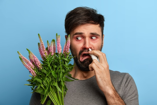 Unhappy man feels unwell, being allergic to pollen, suffers from allergy to plants, uses nasal spray for nose, needs medical treatment, poses over blue wall, cures rhinitis. medical concept.