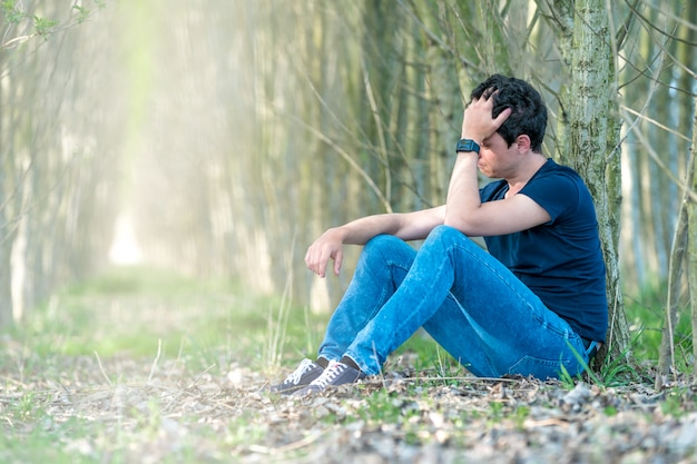 Unhappy man in the forest suffers from depression and frustration of life. copy space