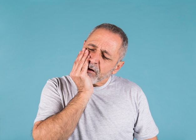 Unhappy man having toothache and touching his cheek