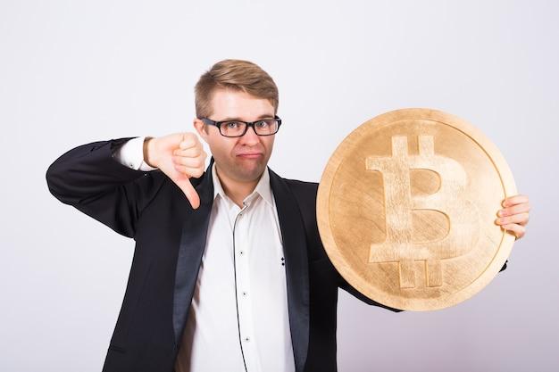 Несчастный человек держит золотой биткойн и показывает палец вниз. концепция сбоя криптовалюты