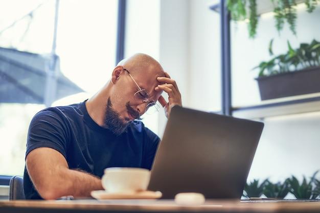 불행한 남자는 머리를 손에 들고 피곤한 사업가는 노트북을 들고 업무용 책상에 앉아 두통을 느낀다