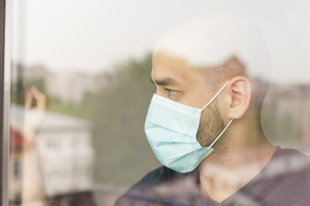 Unhappy man looking through window wearing protection mask during self isolation