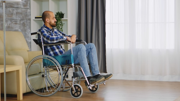 Unhappy man in wheelchair in living room looking at window.
