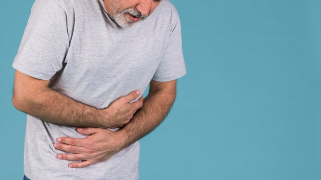 Unhappy man with abdominal pain on blue backdrop
