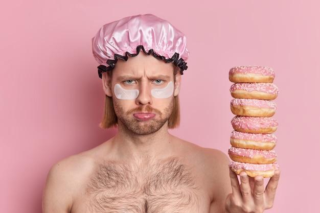 憂鬱な表情の不幸な男がトップレスの屋内に立って甘いドーナツの山を保持し、目の下のしわを減らすためにコラーゲンパッチを適用します。
