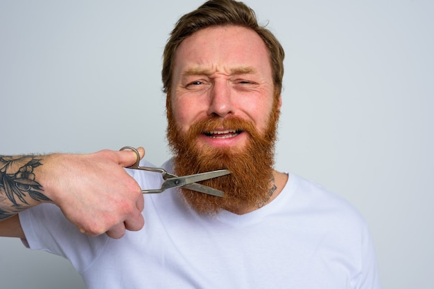 Unhappy man with scissors doees not want to cut the beard