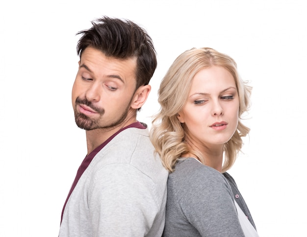 Unhappy man and woman are standing back each other.
