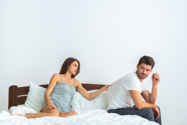 The unhappy man and a woman sitting on the bed on the white background