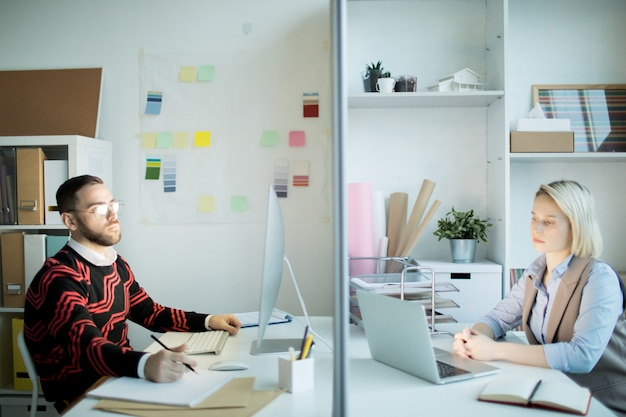 Unhappy marketing specialists working in office