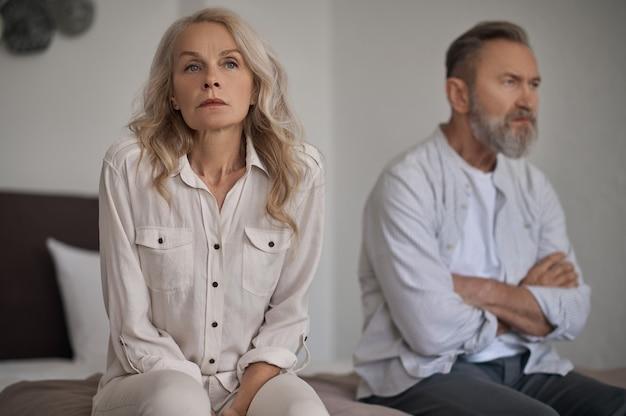 沈黙の中で離れて座っている不幸な成熟したカップル