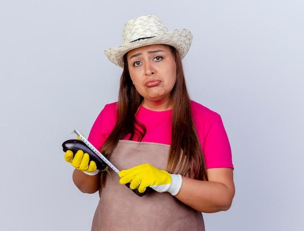 Infelice donna di mezza età giardiniere in grembiule e cappello che indossa guanti di gomma che tengono melanzane fresche misurandolo con un metro a nastro guardando la fotocamera con espressione triste in piedi su sfondo bianco